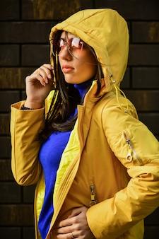 Modello di moda che guarda l'obbiettivo. ritratto di moda stile di vita all'aperto. camminando sulla città d'autunno. indossare capispalla eleganti e luminosi. ragazza alla moda con gli occhiali. ritratto di bella ragazza in giacca autunnale.