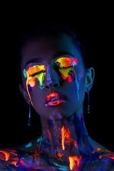 Modello di moda in luce al neon con vernice fluorescente.