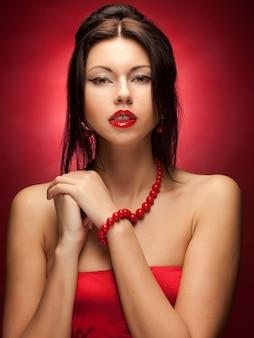 Modello di moda in posa su sfondo rosso