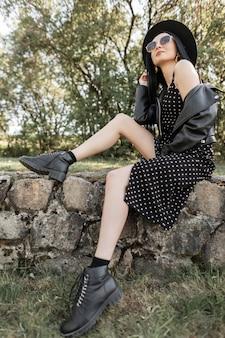 Modello di moda bella giovane donna in occhiali da sole in bel cappello in abiti stagionali neri casual alla moda dalla nuova collezione di giovani alla moda posa sulle pietre in una luminosa giornata di sole nel parco. ragazza sexy.