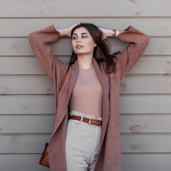 Moda modello sexy giovane donna alla moda in vestiti alla moda raddrizza i capelli in piedi vicino alla parete dell'annata in città. attraente ragazza in cappotto in pantaloni in camicia pone sulla strada vicino all'edificio in legno.