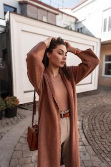 Moda modello sexy giovane donna in abiti stagionali alla moda raddrizzare i capelli in piedi in città il giorno di primavera. bella bella ragazza in abito elegante con borsa in pelle in posa all'aperto. signora urbana.