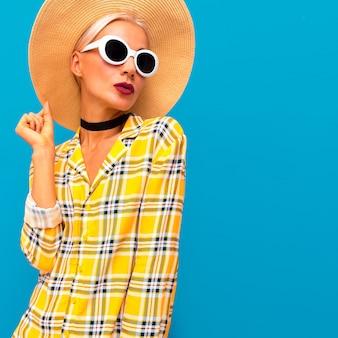 Modella con cappello di paglia e camicia a scacchi. accessori alla moda country