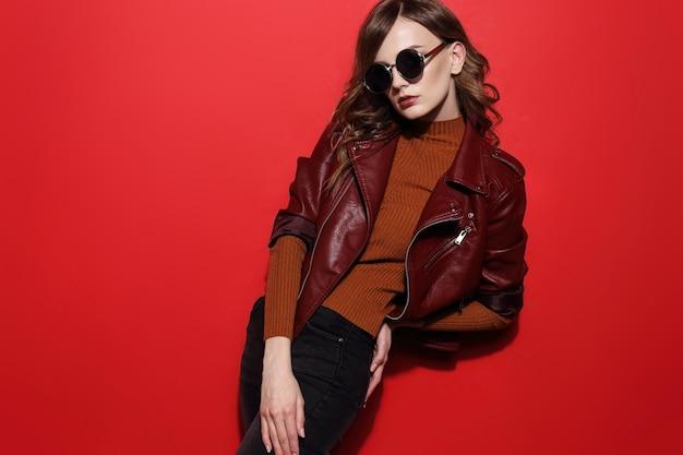 Modello di moda in occhiali da sole, bella giovane donna. giacca di pelle, girato in studio, sfondo rosso