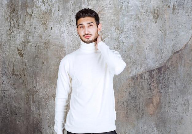 Modello di moda in maglione bianco in piedi sullo sfondo del muro di cemento e sembra confuso o pensieroso