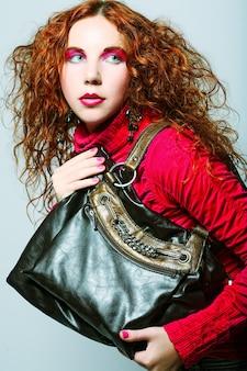 Modello di moda con borsa. in posa in studio