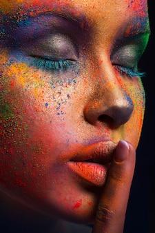 Modello di moda con trucco colorato mostra segno di silenzio. bella donna con trucco creativo splash, raccolto