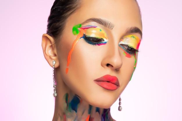 Modello di moda con vernice colorata sul viso.