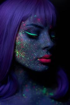 Modello di moda donna in trucco fluorescente luminoso al neon, capelli lunghi, goccia sul viso