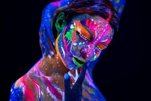 Modello di moda donna in luce al neon, ritratto di ragazza bellissima modella con trucco fluorescente, body art in uv, faccia dipinta, trucco colorato, su sfondo nero