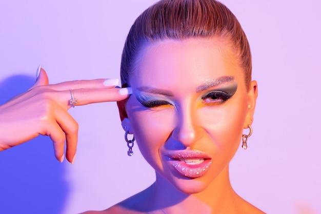 Modello di moda donna con un trucco luminoso alla luce intensa colorata è in posa in studio.