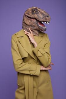 Modello di moda in maschera di dinosauro tyrannosaurus rex mantello giallo senape su sfondo viola