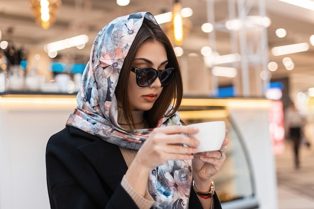 Modello di moda giovane bella donna in elegante scialle di seta in occhiali da sole alla moda in cappotto nero alla moda con una tazza di caffè è si siede nella caffetteria nel centro commerciale. attraente ragazza moderna gode di una bevanda calda al chiuso