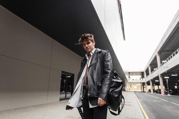 Giovane modello di moda in un'elegante giacca di pelle nera in una camicia in jeans con uno zaino alla moda con un'acconciatura in posa vicino alla strada in città. hipster ragazzo americano si trova in strada.