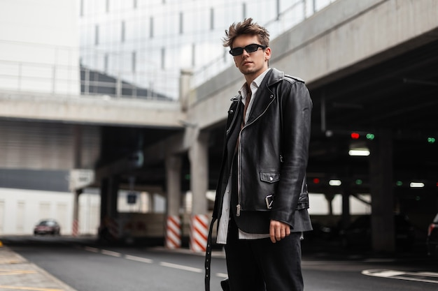 Modello di moda giovane uomo moderno in occhiali da sole vintage in una giacca elegante in pelle nera in jeans si trova sul parcheggio all'aperto. ragazzo sexy hipster cool americano per strada in città. stile retrò.