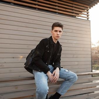 Modello di moda giovane uomo alla moda in vestiti di jeans alla moda si siede