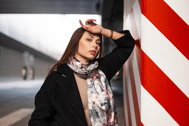 Modello di moda giovane donna con capelli castani con pelle pulita sana con labbra sexy in abiti eleganti sta riposando vicino al pilastro dell'annata in linea rosso-bianca all'aperto. ragazza moderna attraente. signora di bellezza.