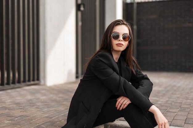 Modello di moda giovane donna con labbra sexy in eleganti occhiali da sole in vestiti neri alla moda della nuova collezione alla moda giovanile sta riposando vicino all'edificio in città. cool splendida ragazza hipster sedersi all'aperto.