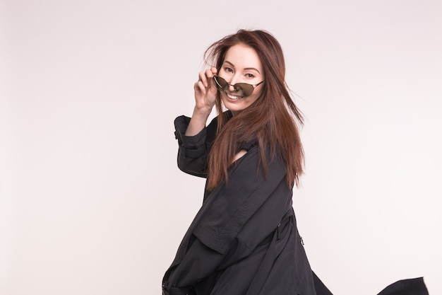 Concetto di moda, modellismo e persone. giovane donna asiatica ti guarda da sopra gli occhiali su bianco.