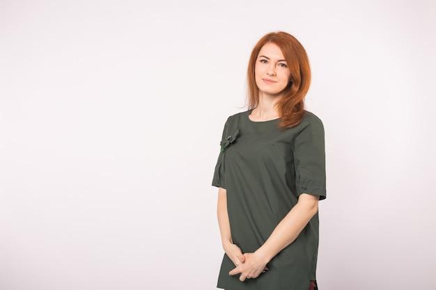 Concetto di moda, modellismo e persone. giovane donna testa rossa in piedi sul bianco con copia spazio