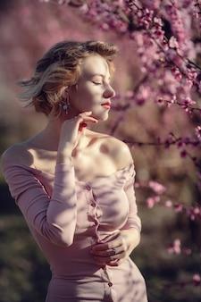 Foto di moda all'aperto di splendida giovane donna in abito elegante in posa in giardino con alberi di pesco in fiore. bionda nei giardini fioriti