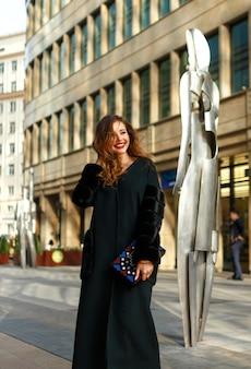 Foto di moda all'aperto di donna sensuale con capelli rossi in abiti eleganti e cappotto lussuoso, camminando per città.