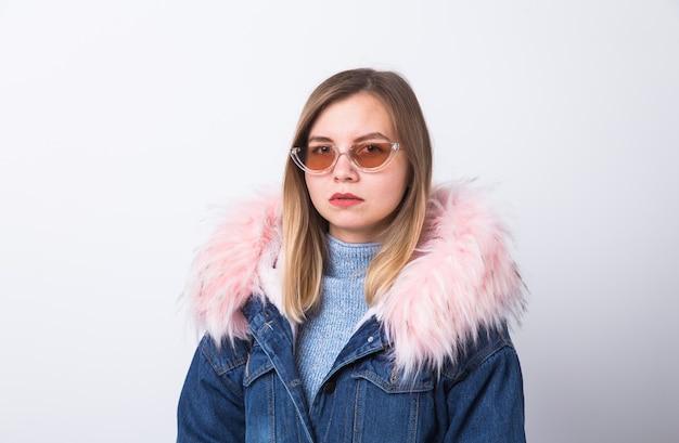 Moda, persone e concetto di stile urbano invernale - giovane donna in abiti alla moda sul muro bianco.