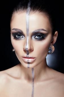 Trucco perfetto alla moda, fascia color argento sul viso della ragazza, sopracciglia argentate e capelli castani neri.