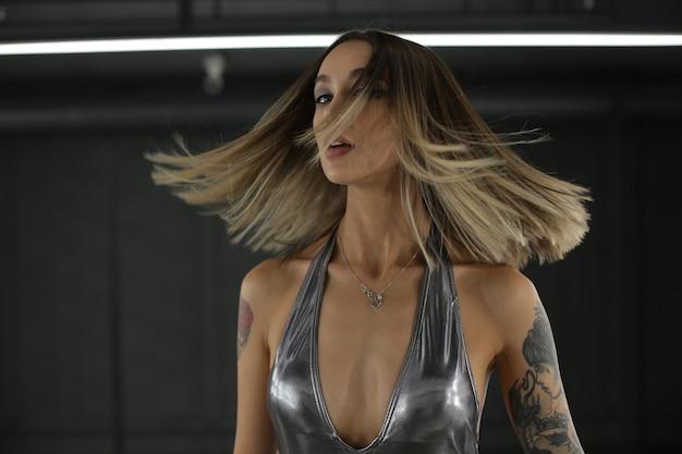 Foto di moda di una bella ragazza sensuale con i capelli biondi in una lussuosa tuta d'argento in posa al chiuso che scatta foto di alta qualità