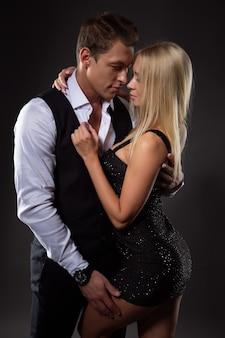 Foto di moda su uno sfondo scuro di una coppia elegante in una tenera passione
