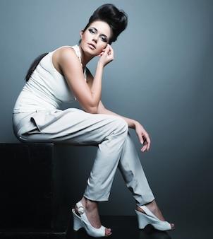 Foto di moda, un modello è in posa su sfondo grigio