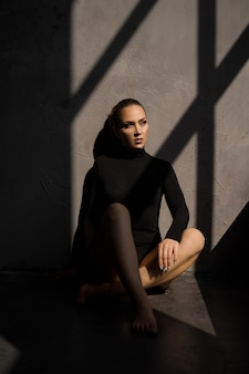 Foto di moda di donna sensuale si siede sul pavimento accanto alla finestra un'ombra su di lei