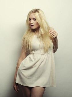 Foto di moda di giovane donna magnifica in vestito bianco.