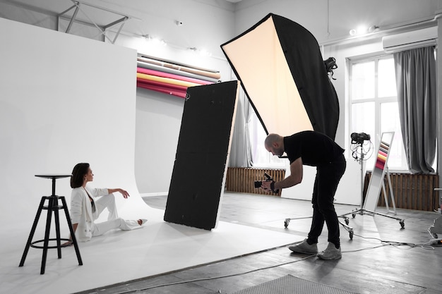 Fotografia di moda in uno studio fotografico. fotografo maschio professionista che scatta foto del modello di bella donna sulla fotocamera, dietro le quinte