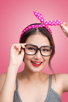 Moda ritratto di ragazza asiatica con occhiali da sole in piedi su sfondo rosa.