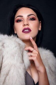 Moda ritratto di una bella ragazza bruna in pelliccia con accessori di lusso. modello di bellezza con gioielli su sfondo nero. ragazza in pelliccia di visone bianca. bella donna di inverno di lusso.
