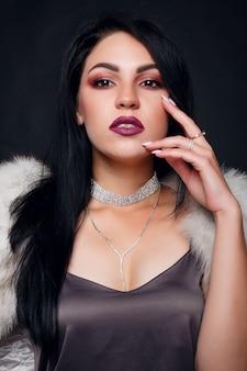 Moda ritratto di una bella ragazza bruna in pelliccia con accessori di lusso