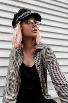 Ritratto di moda di una bella ragazza hipster in elegante abito casual con occhiali rotondi vintage e un cappello si siede vicino a una casa di legno