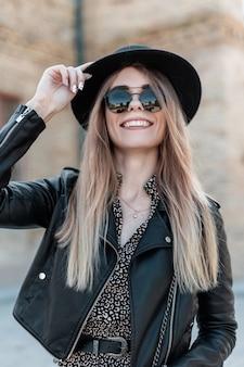 Moda ritratto di una bella giovane donna felice in un abito vintage con una giacca di pelle e occhiali da sole alla moda cammina per strada in una giornata di sole