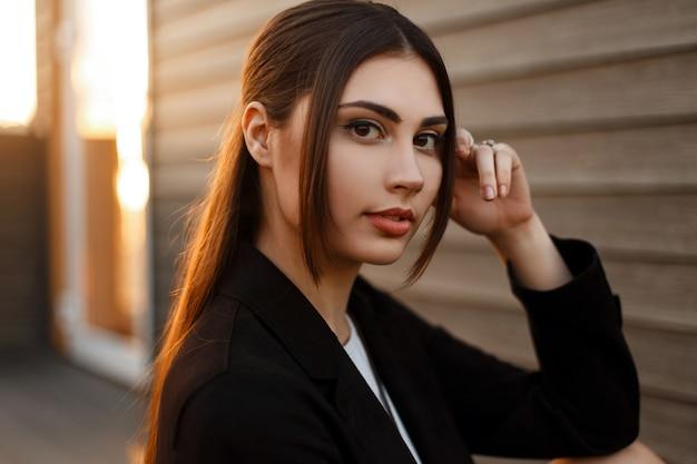 Moda ritratto di una bellissima giovane donna in un cappotto nero al tramonto