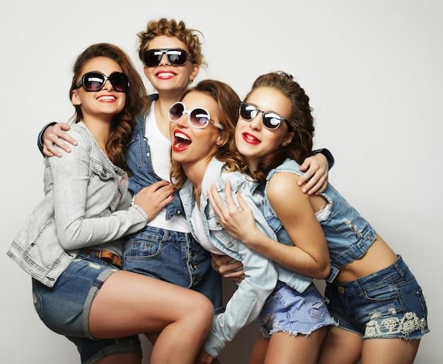 Moda ritratto di quattro ragazze alla moda hipster migliori amici, su grigio. tempo felice per il divertimento.