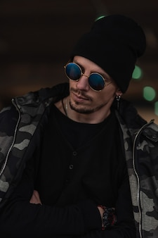 Moda ritratto di bel ragazzo modello hipster con occhiali da sole alla moda e cappello nero in giacca invernale militare e pullover in città