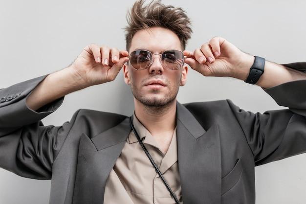 Ritratto alla moda di un bell'uomo modello con barba corta in abito casual alla moda con un blazer e una camicia guarda attraverso gli occhiali da sole vicino a un muro grigio