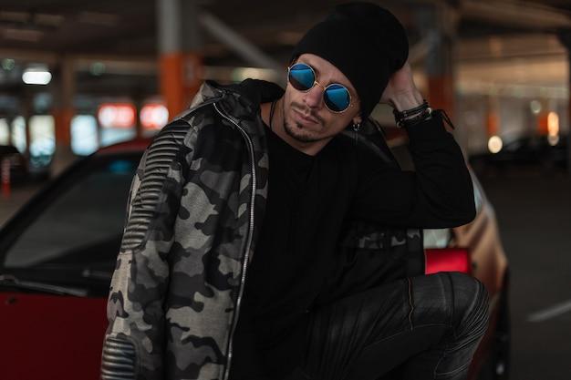 Moda ritratto di bel giovane con occhiali da sole stile e cappello nero in giacca militare invernale con pullover in città. stile casual maschile urbano