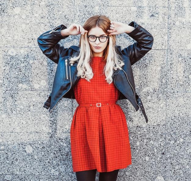 Moda ritratto di donna hipster in abito estivo casual elegante in posa sullo sfondo della parete.