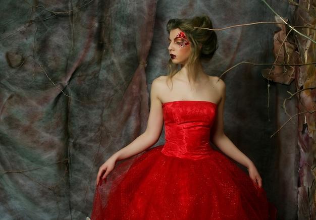 Ritratto di moda di una bella ragazza romantica con acconciatura, labbra rosse, abito artistico