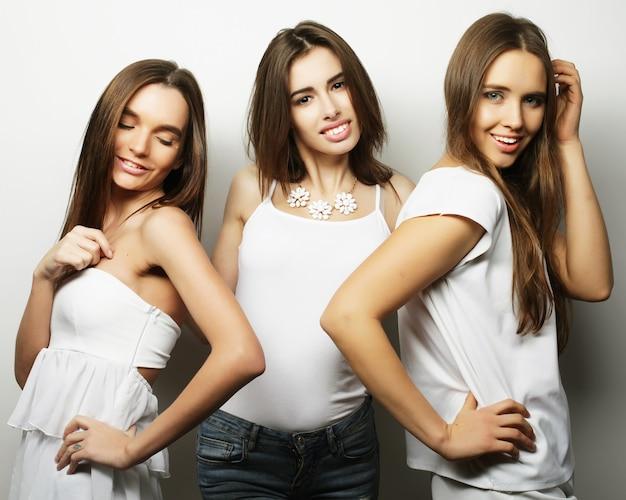 Moda ritratto di tre migliori amiche ragazze alla moda, su bianco. tempo felice per il divertimento.