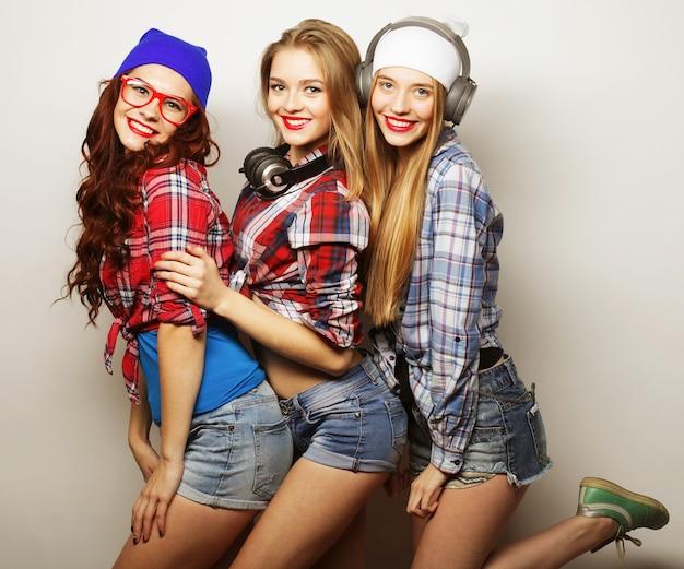 Moda ritratto di tre migliori amici di ragazze hipster sexy alla moda, sopra fondo grigio tempo felice per il divertimento.