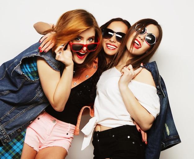 Moda ritratto di tre migliori amiche di ragazze hipster sexy alla moda, su sfondo grigio. tempo felice per il divertimento.