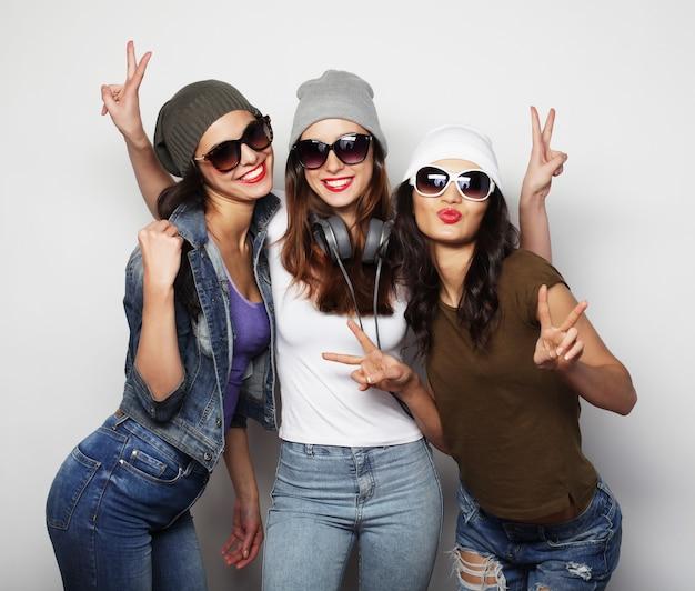 Moda ritratto di tre migliori amiche ragazze hipster sexy alla moda, su superficie grigia. tempo felice per il divertimento.